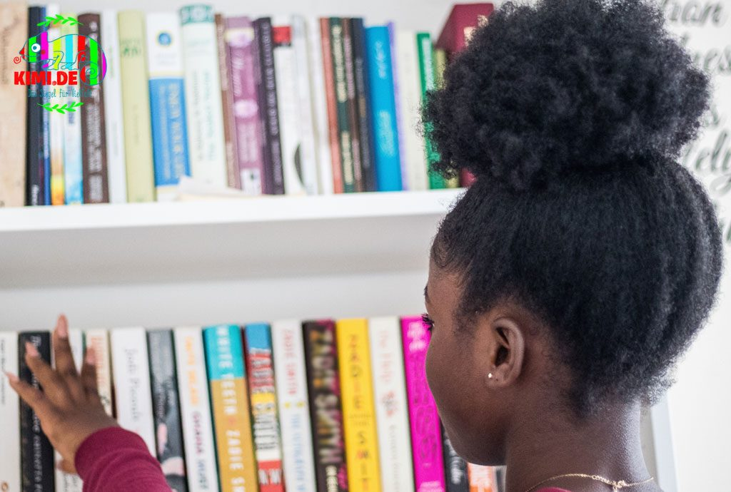 Ein Mädchen of Color betrachtet ein Bücherregal.